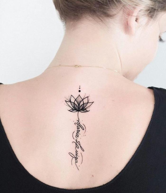 lotusblume tattoo am rücken, kleiner lotus in kombiantion mit schriftzug, blackwork tätowierung