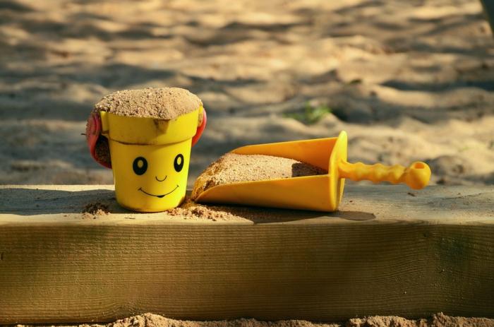 ein gelbes Eimerchen mit einem Gesicht, das lächelt, voller Sand und in gelber Farbe