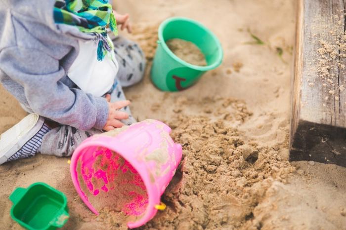 Sandkasten, rosa und grünes Eimerchen, ein Kind spielt im Sand, Rand aus Holz