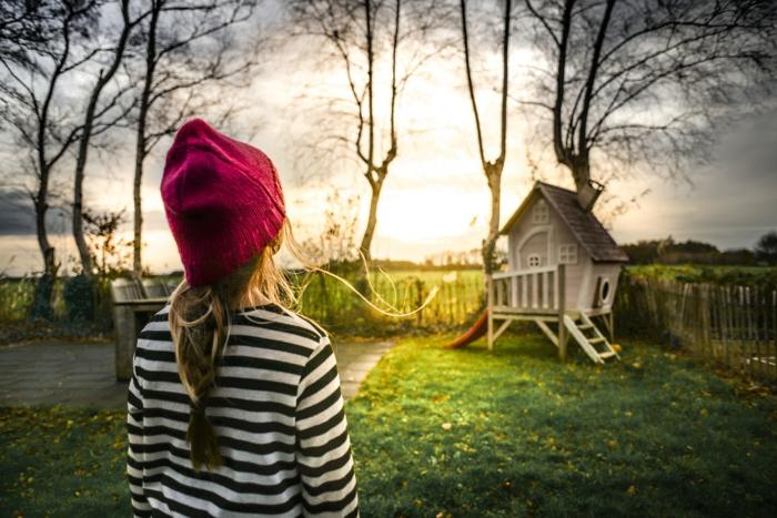 ein Spielhaus im Garten, ein Spielplatz im Garten, ein Mädchen will damit spielen