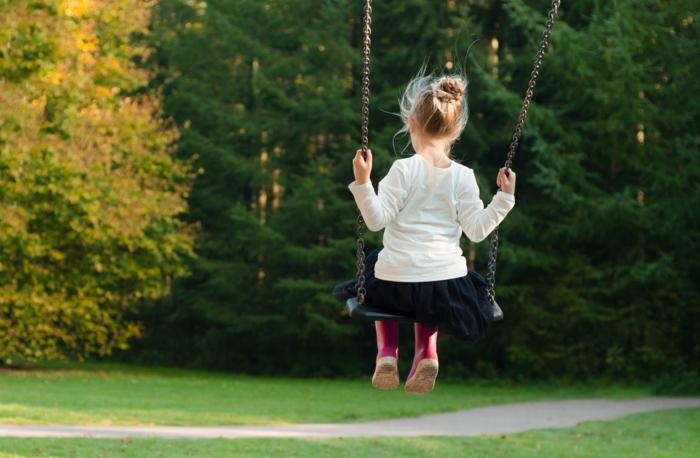 ein Mädchen schaukelt in einem grünen Garten auf einem Spielplatz