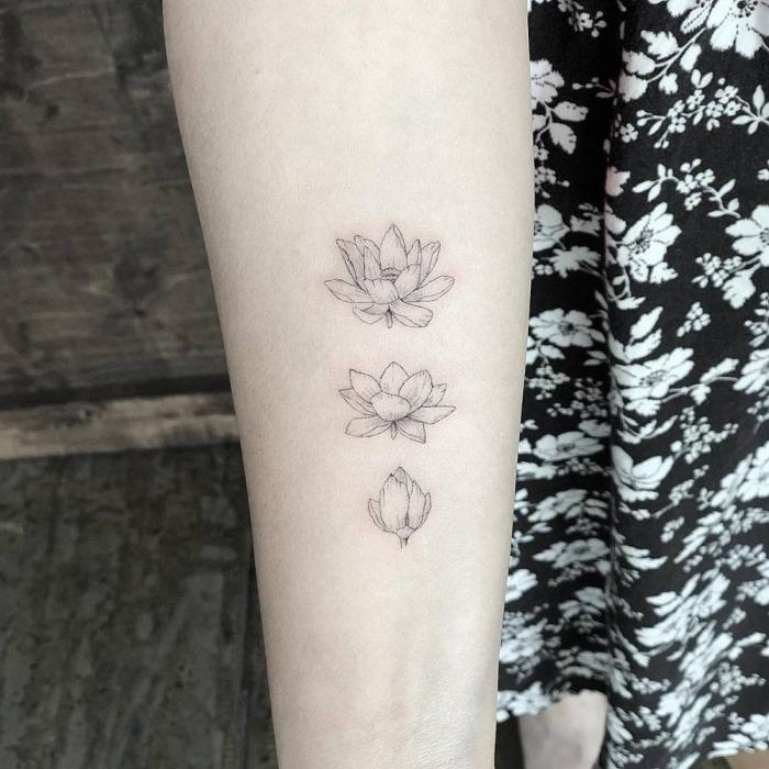 symbol für neuanfang, drei blumen am oberarm, kleine tattoo motive für frauen, tätowierung