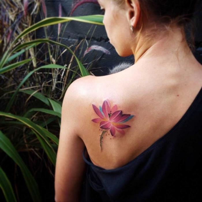 symbol für neuanfang, frau mit farbigeer tätowierung am rücken, rosa lotus, wasserfarben blume