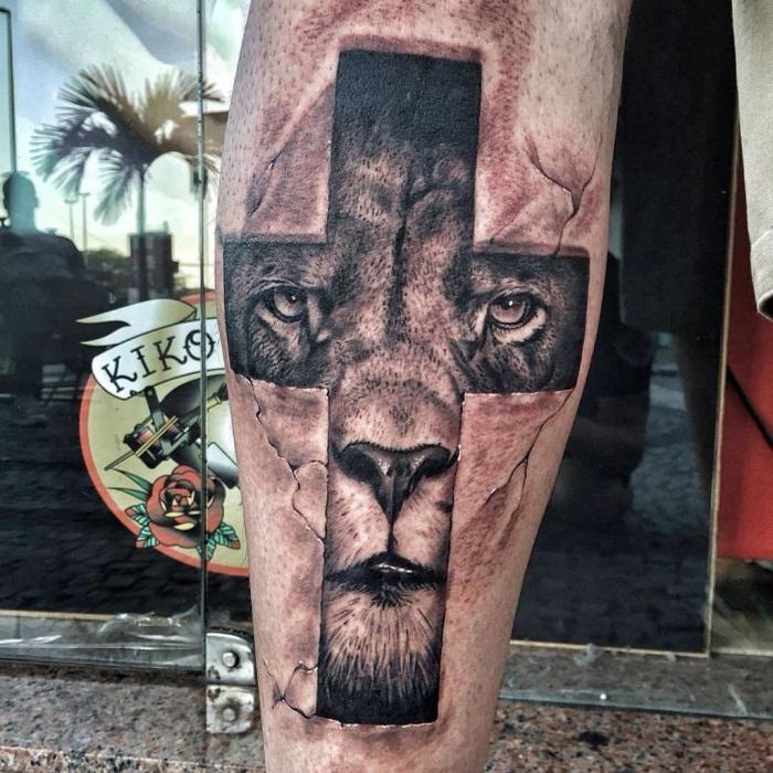 tattoo bedeutung, symbol für stärke, läwenkopf als motiv, löwe im kreuz, schwarz graue tätowierung am bein