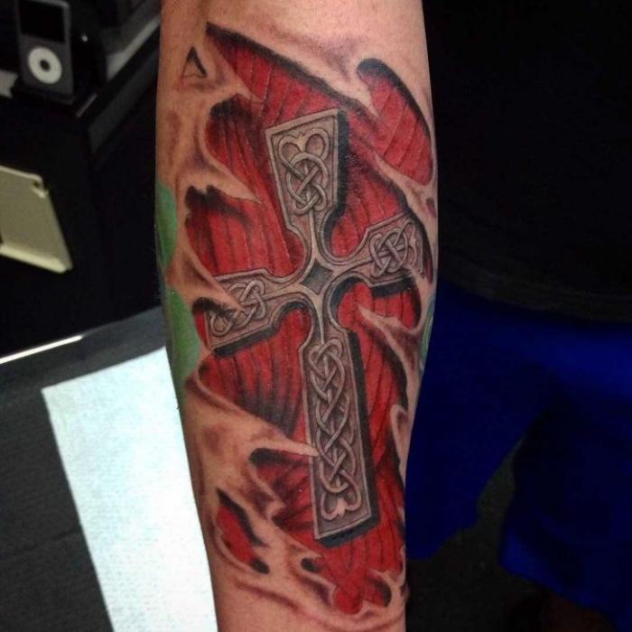 tattoo bedeutung, zerrissene haut, eisernes kreuz, farbige tätowierung am bein, keltrische motive, muskel