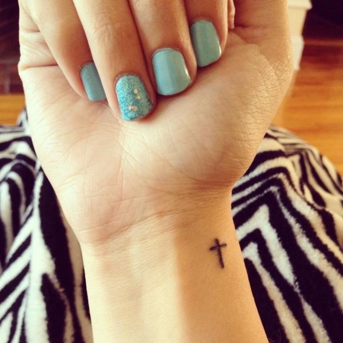 tattoo ideen klein, hellblauer nagellack mit glitzer, kleines kreuz am handgelenk, kurze nägel, sommer maniküre