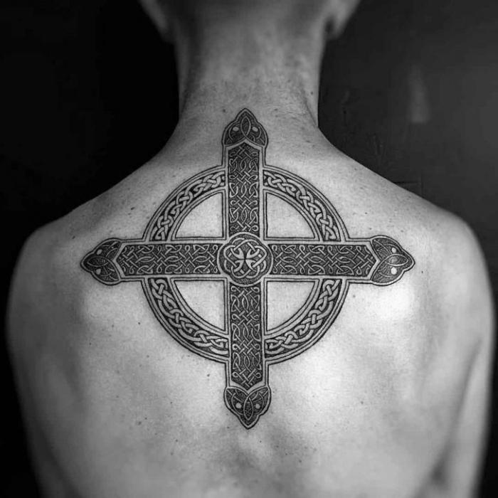 tattoo kreuz, mann mit großer schwarz grauer tätoweirung mit keltischen motiven am rücken, symbol