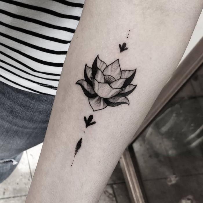 tattoo lotusblüte, frau mit blakcwork tätowierung am unterarm, lotus am arm, tattoos mit bedeutung