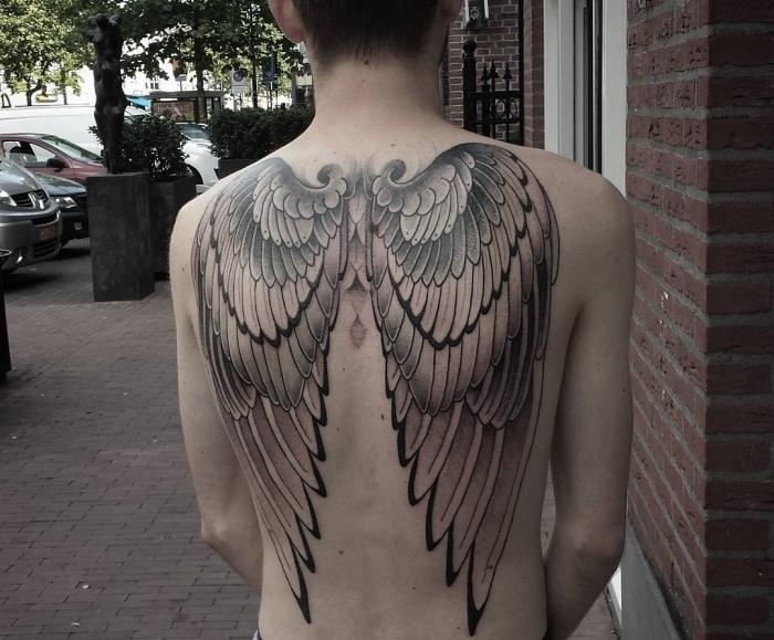 mann mit großer tätowierung mit flügel motiv, tattoo männer rücken, tattoo foto