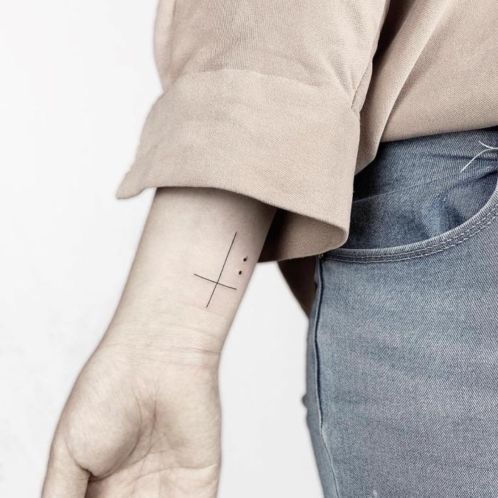 simples kreuz mit zwei punkten, tätowierung am arm, tattoo motive klein, unterarm, frau