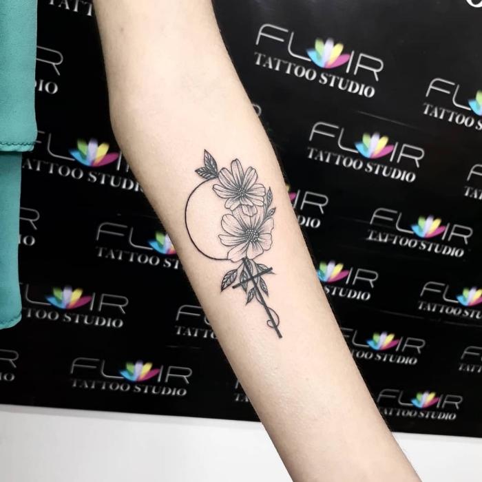 tattoo motive klein, kreuz in kombination mit kreis und blumen, schwarz graue tätowierung am arm