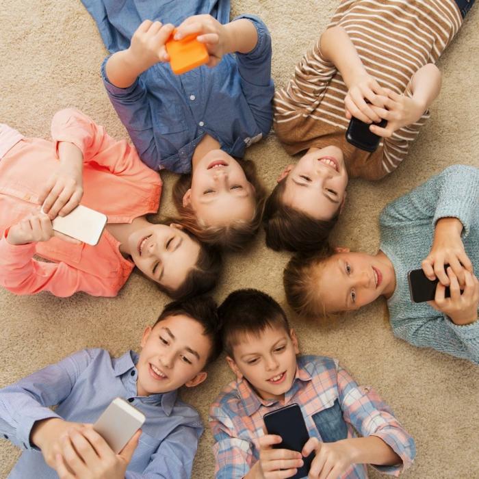 YouTube Kids, eine kleine Gruppe von Kinder, die auf dem Boden mit Handys spielen