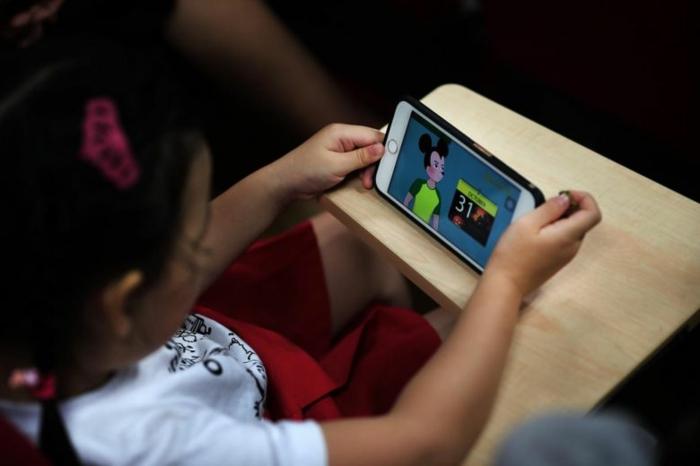 ein Mädchen spielt mit dem Smartphone und sieht gerade YouTube Kids