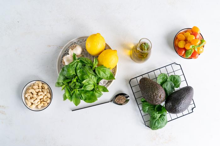 Zutaten für Baslikum Pesto, Basilikum und Avocado, Zitrone und Knoblauch, Cashews und Cherrytomaten