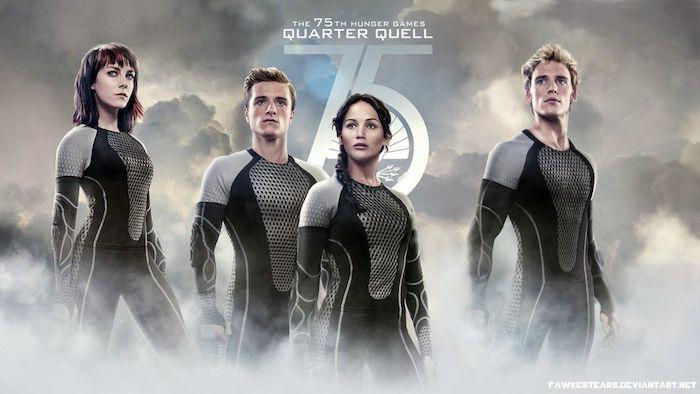 hungerspiele, die tribute von panem, ein poster von dem hunger games film, zwei frauen und zwei männer mit schwarzen kostümen, himmel mit grauen wolken