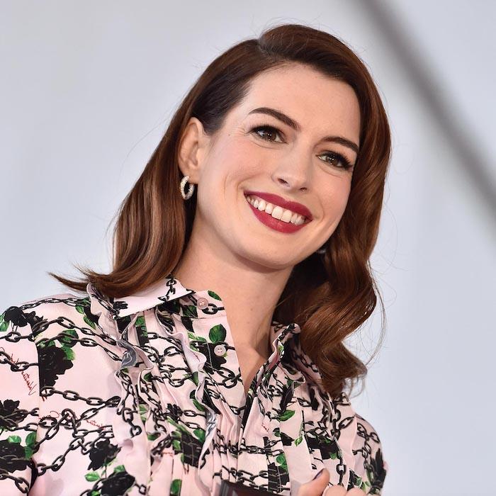 Anne Hathaway mit offenen gewellten Haaren, rotem Lippenstift, schwarzer Mascara