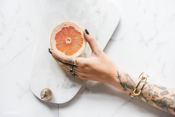 Viele Tattoos am Arm, schwarzer Nagellack, silberne und goldene Ringe, halbierte Grapefruit