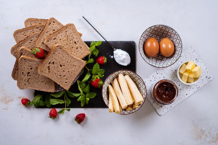Zutaten für French Tost Roll-Ups, Banane und Schokoaufstrich, Eier und Butter, Vollkornbrot und Puderzucker