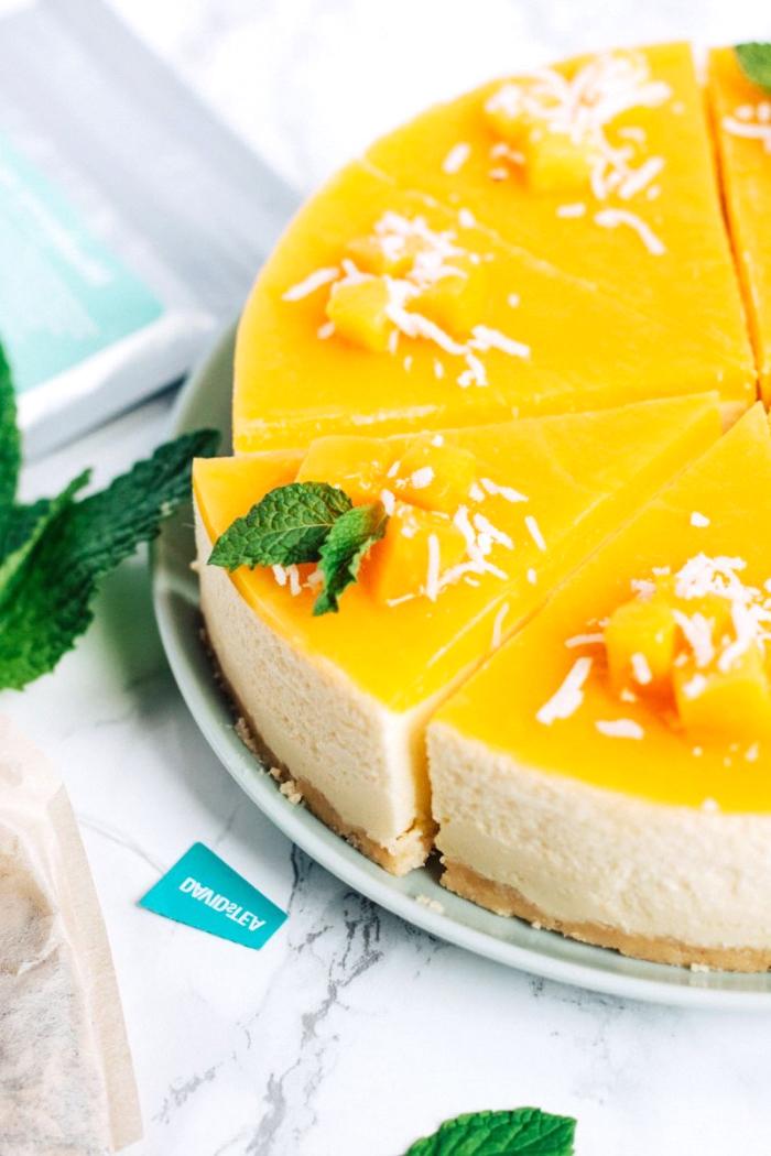 ausgefallene torten rezepte, frischkäsekuchen mit mango garniert mit kokosflocken und kleinen früchten, philadelhia torte