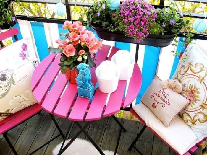 balkon dekorieren, ideen zum entlehnen, ein rosaroter tisch mit blumen darauf, lila hängeblumen, stühle mit kissen deko