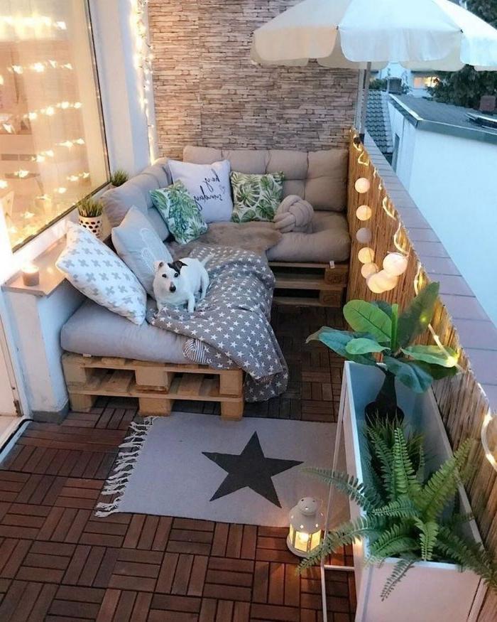 balkon ideen, dekor lampen, teppiche, paletten sofa mit kissen, ein hund liegt auf dem sofa