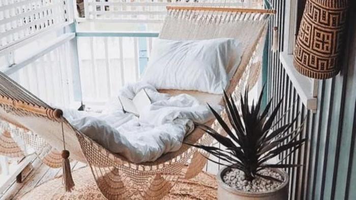 balkon deko zum chillen, einen schönen hammock mit kissen, decke und deko in beige zum entspanen von den augen