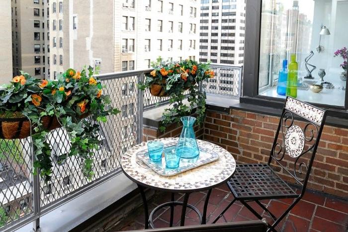 balkongestaltung, spanischer style, fließen möbel und deko, blumen in orange, glas geschirr