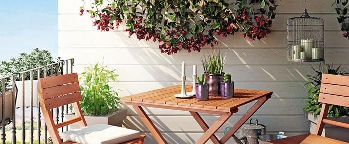 kleiner balkon gestalten, holzmöbel mit deko kerzen auf dem tisch und kleine blumentöpfe mit kaktus u a