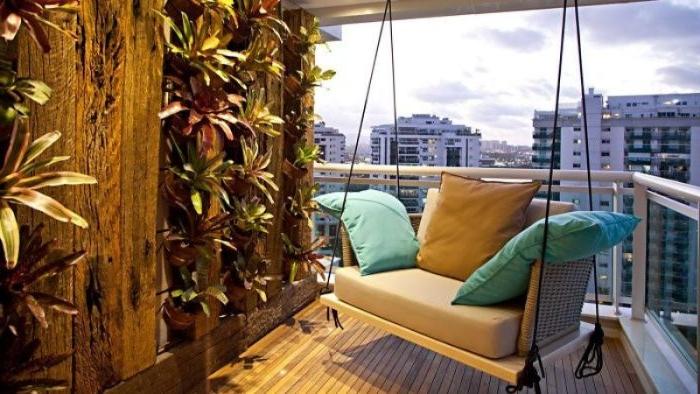 kleinen balkon gestalten, eine schaukel auf dem balkon, viele kissen deko ideen mit pflanzen an der wand