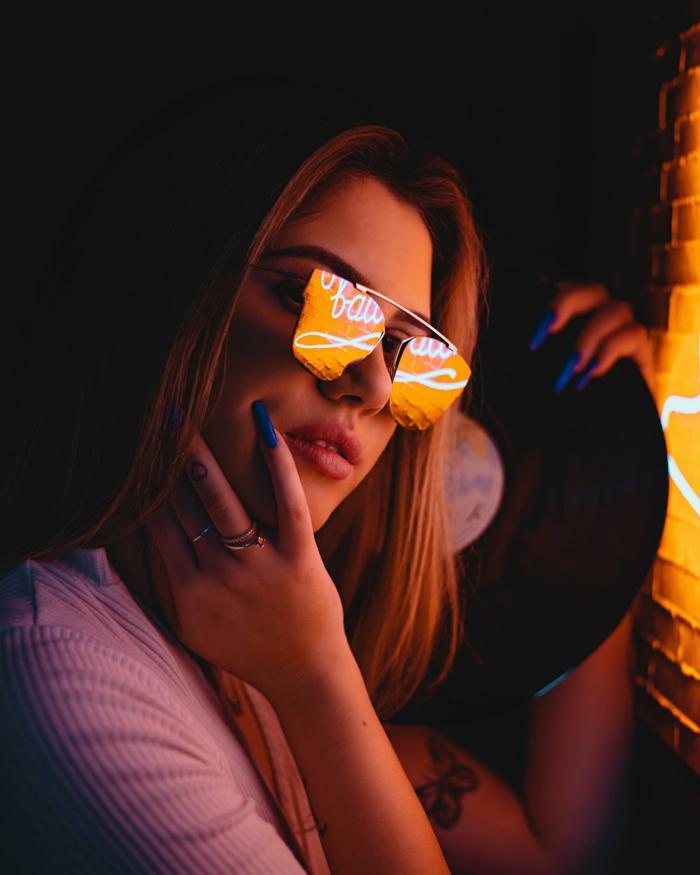 ein Mädchen mit einem Tattoo von Schmetterling an dem Arm, eine Sonnenbrille und Schallplatte