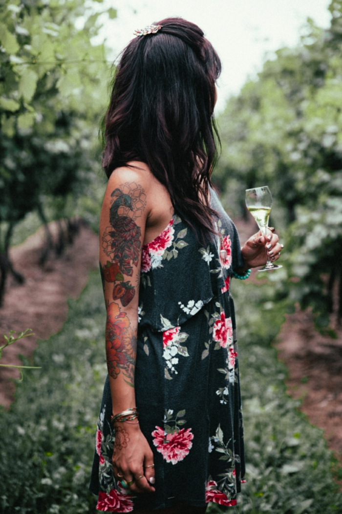 ein Mädchen mit vielen Tattoos, ein schwarzes Kleid mit Blumenmotiven versehen