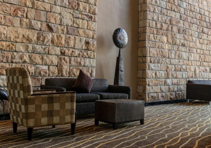 ein Haus mit Steinteppich als Bodenbelag, bunte Möbel, Steinwände, seltsame Skulptur
