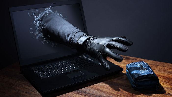 neuer phishing trick, ein laptop mit schwarzem bildschirm, eine hand mit handschuh aus ledder und ein brauner tisch aus holz