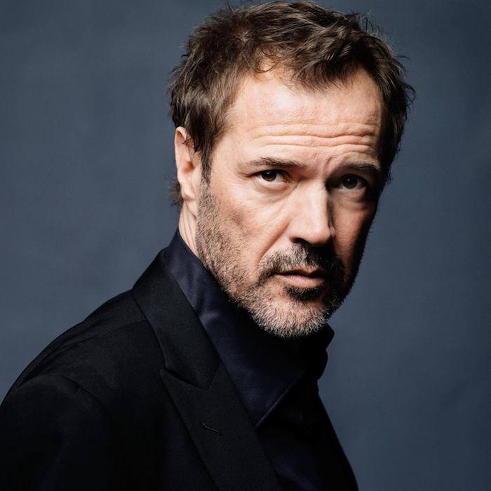 der schauspieler sebastian koch, ein mann mit bart und einem schwarzen hemd