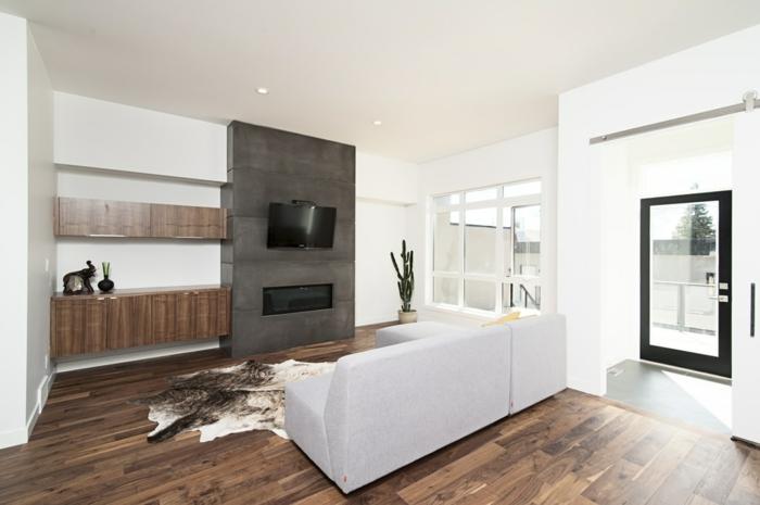 Holz als natürlicher Baustoff, ein weißes Sofa und ein Parkettboden, ein Teppich