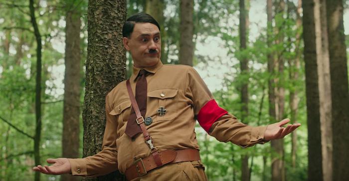 der schauspieler taika waititi als adolf hitler, ein mann mit einer braunen krawatte, szene aus dem film jojo rabbit, ein wald mit grünen bäumen
