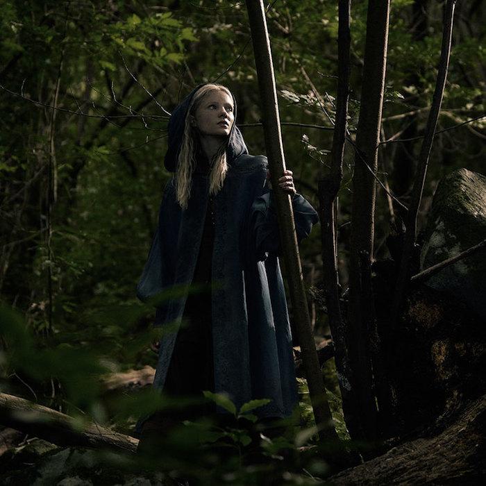 eine junnge frau mit blondem haar in einem wald mit bäumen mit grünen blättern, bild von the witcher von netflix