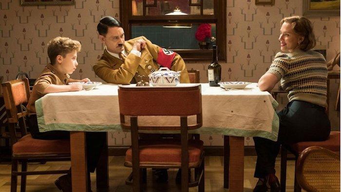 die schauspielerin scarlett johansonn, eine küche mit braunen stühlen und einer tisch und einer weißen decke, ein junge, jojo rabbit