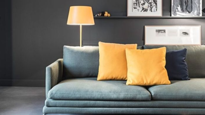 petrol farbe bedeutung, großes sofa in grau, gelbe kissen, eine gelbe stehlampe, zimmergestaltung