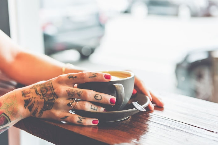 Farbige Tattoos an der Hand, roter Nagellack, herzförmiger silberner Ring, Tasse Kaffee