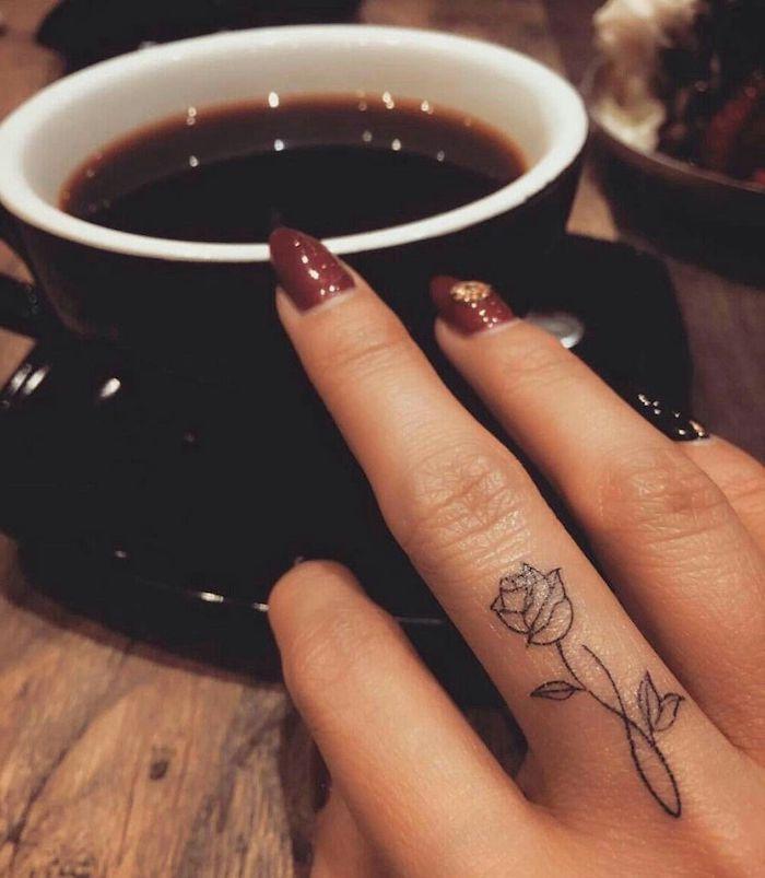 Rosen Tattoo am Mittelfinger, schöne Blumen Tattoos für die Hand, dunkelroter Nagellack mit Kristallen, Tasse Kaffee