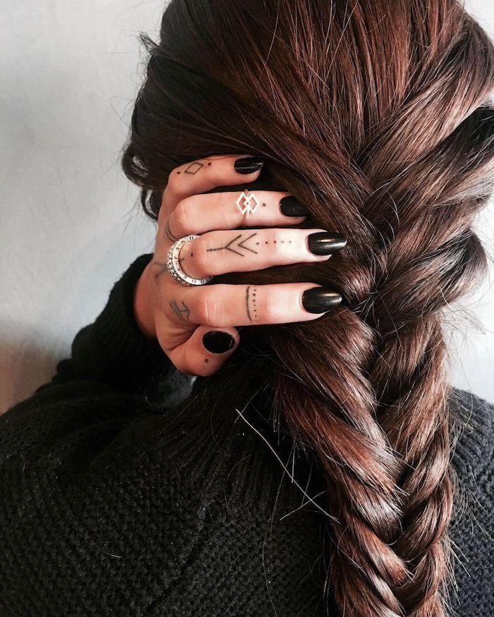 Finger Tattoos, winzige Tattoo Motive, lange dunkelbraune geflochtene Haare, schwarzer Nagellack, schwarzer Pulli