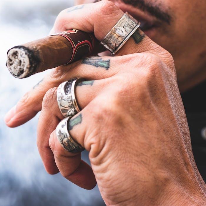 Farbige Finger Tattoos an jedem Finger, massive silberne Ringe, Mann raucht Zigarre
