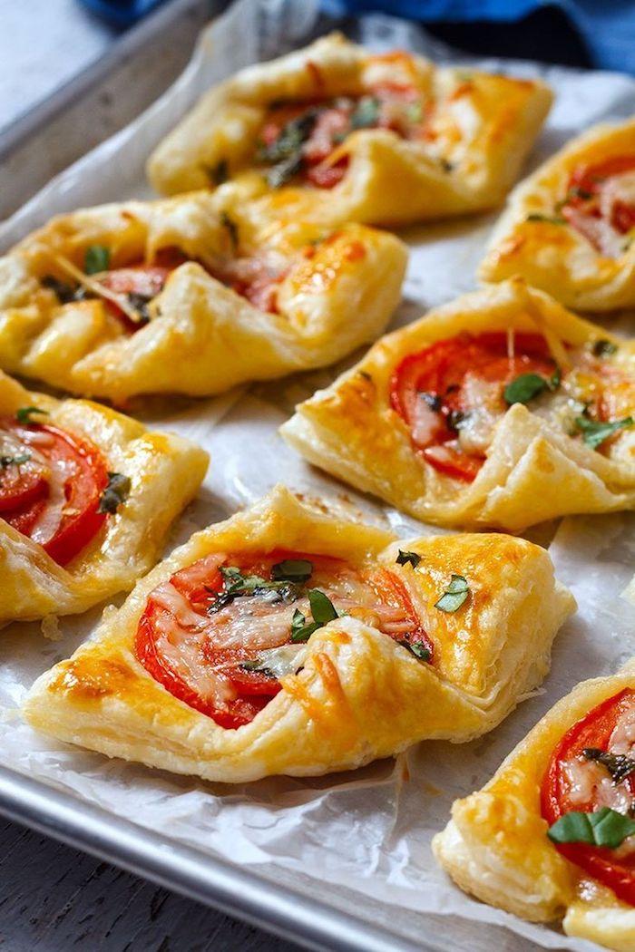 Mini Pizza aus Blätterteig mit Tomatenscheibe und Parmesan, schnelle Snacks für Party