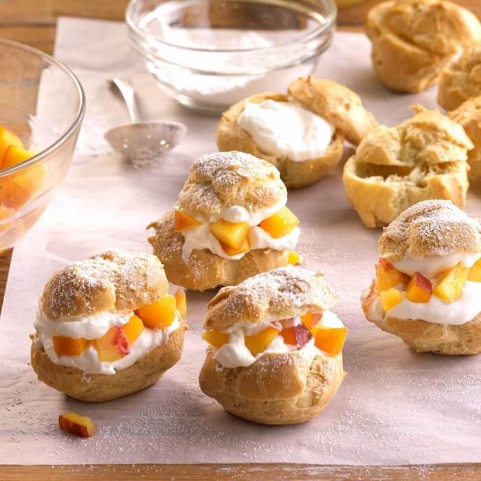 Windbeutel mit Vanillecreme und kleinen Pfirsichstückchen, süße Snacks für Party