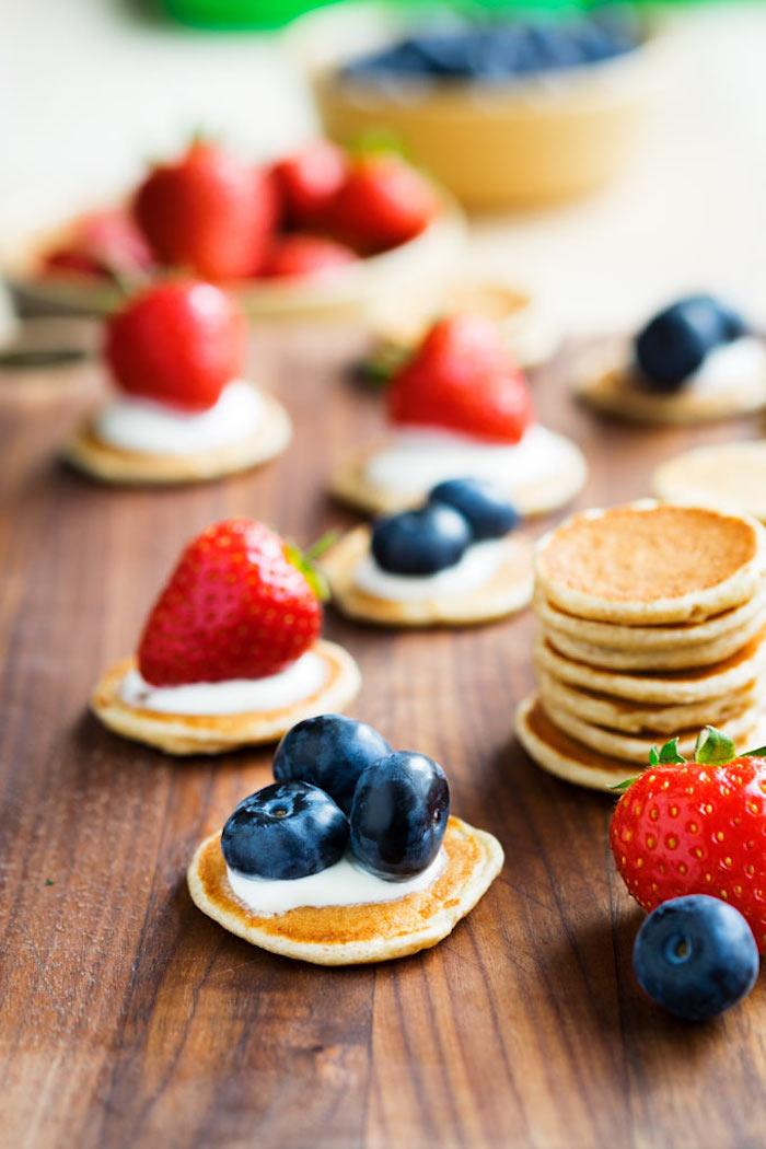 Mini Pfannkuchen mit Vanillecreme, frischen Blaubeeren und Erdbeeren, kleine Häppchen für Party