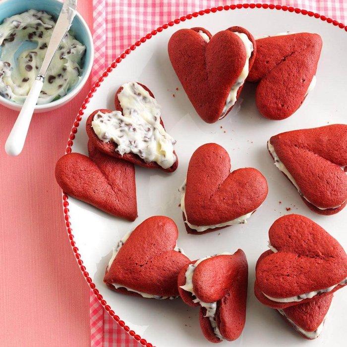 Süße Snacks für Party Gäste, rote Kekse in Form von Herzen, Vanillecreme mit Schokoladenstückchen
