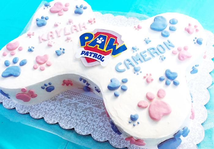 Paw Patrol Torte in Form von Knochen, weiße Torte mit rosa und blauen Pfoten und Paw Patrol Logo
