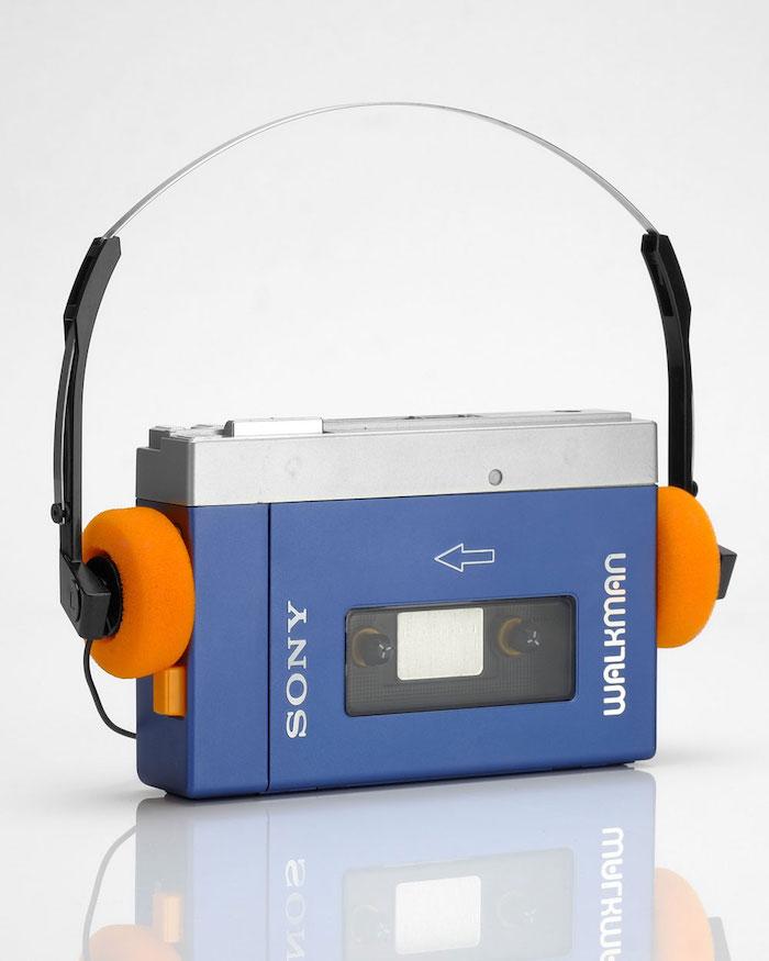 ein kleiner blauer walkman von sony mit kassette und kleinen orangen kopfhörern