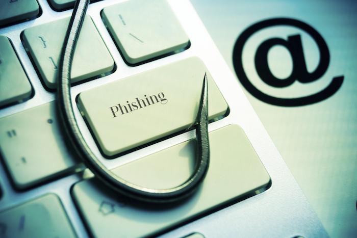 eine angel mit grauem angelhaken aus metall, ein laptop mit weißen tasten, ein neuer phishing trick
